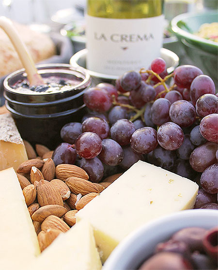 A cheese tray featuring a variety of fresh local cheeses, almonds, olives, red grapes, homemade preserves and crackers