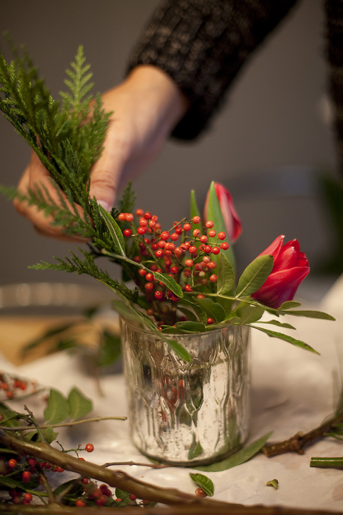 Adding berry sprigs to a natural table runner