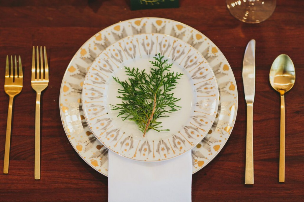 Adding greenery to place settings keeps things festive, a tad rustic, and warm.