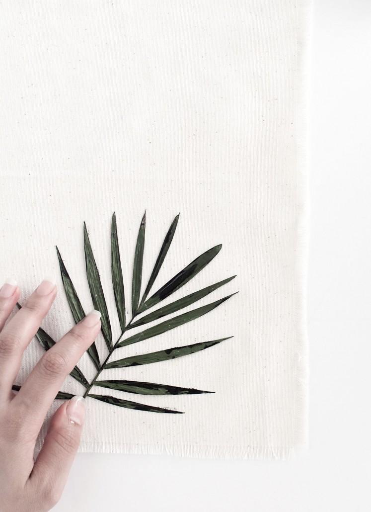 Press the painted palm leaf on the napkin to create DIY Palm Leaf Napkins