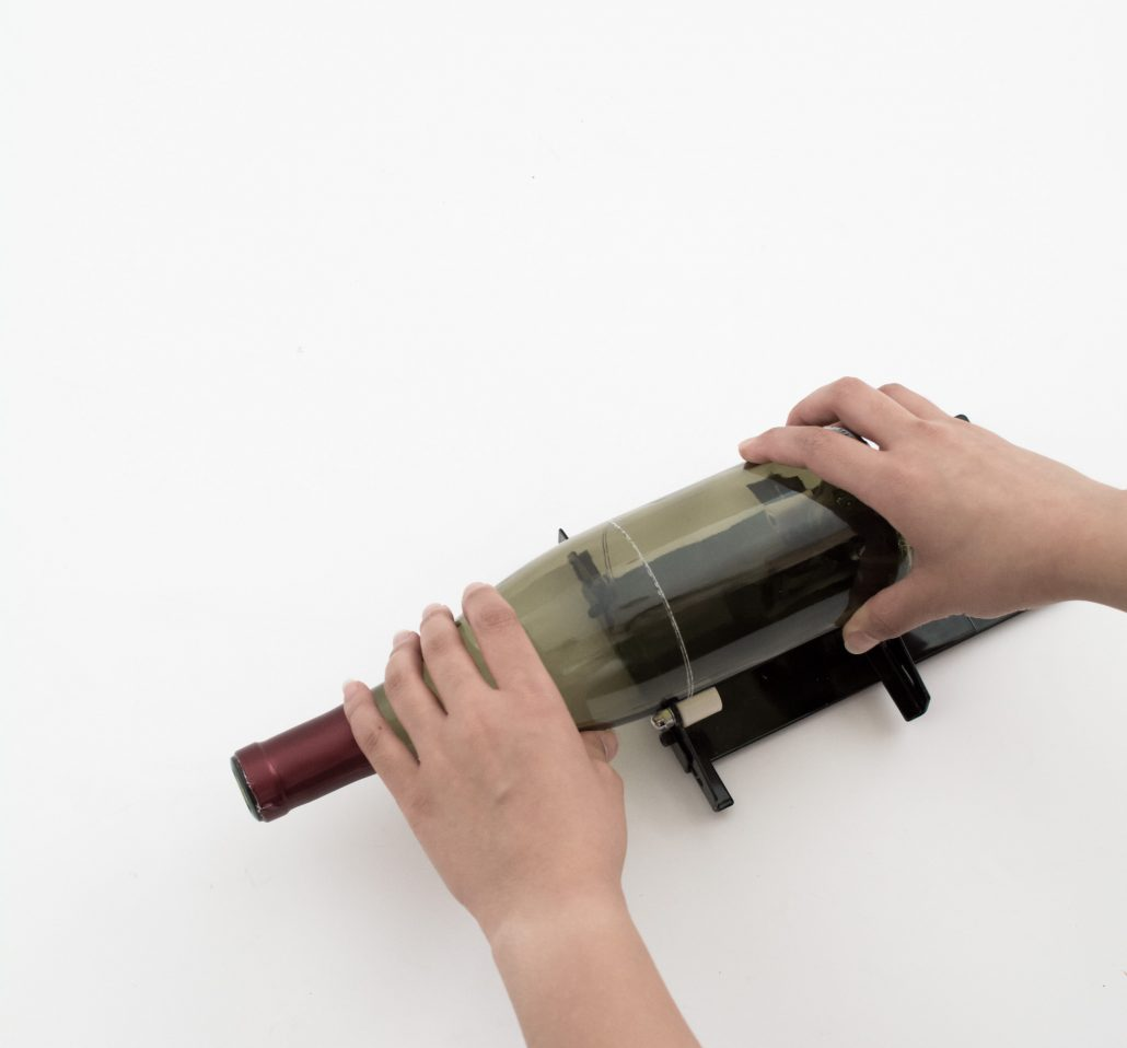 Score the wine bottle with the bottle cutter to make your floating candle holders
