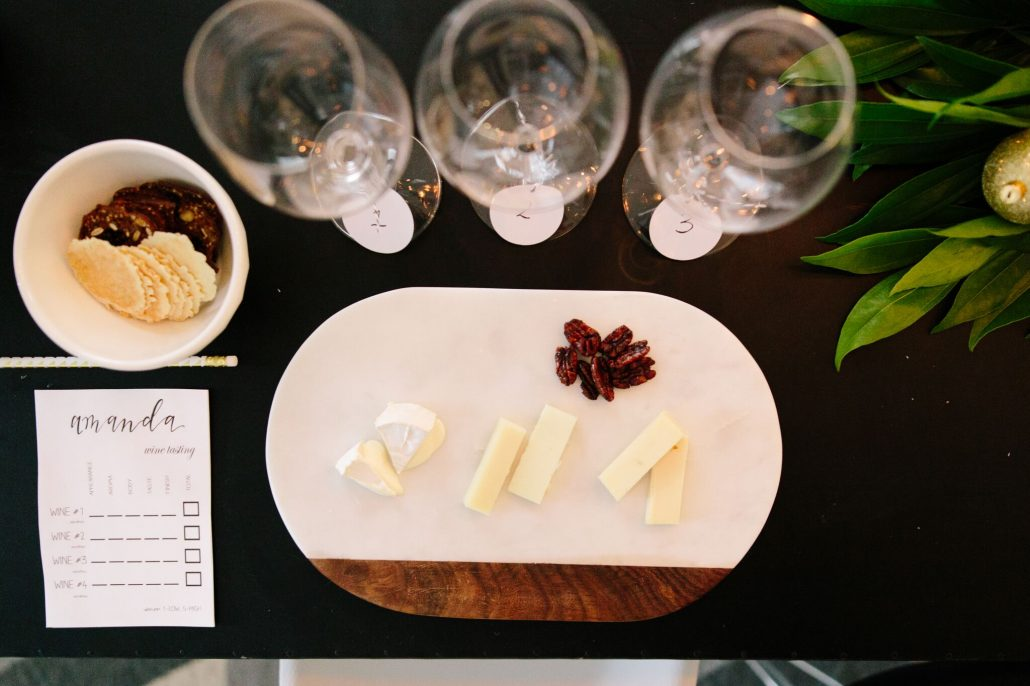 Cheese and accoutrement alongside numbered glasses for a blind wine tasting