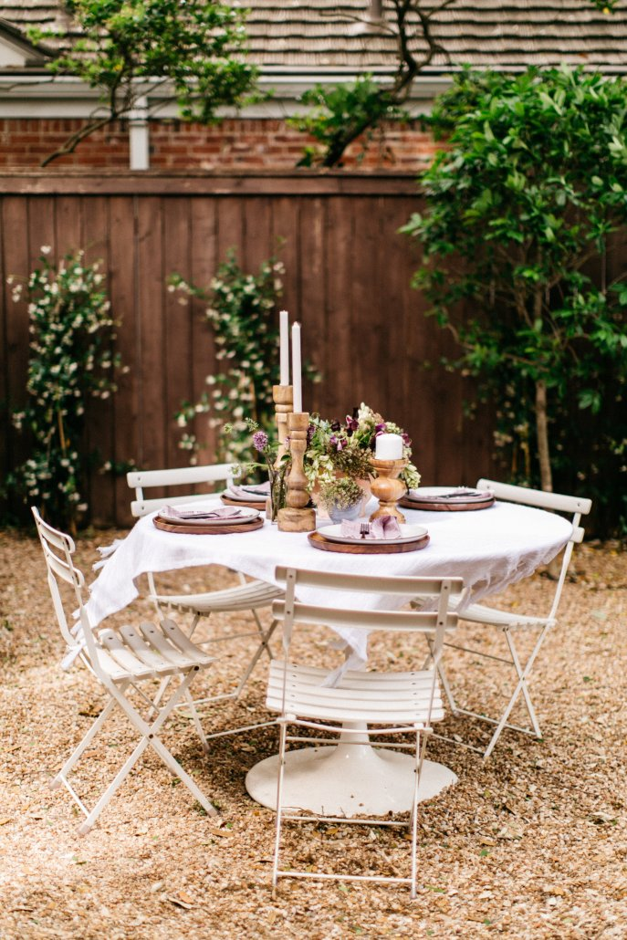 Folding table and chairs in a charming area of the backyard for a low-key dinner party by Camille Styles