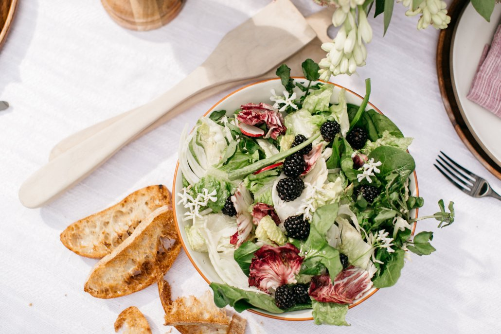 Simple market green salad with fennel, berries and herbs at a low-key dinner party by Camille Styles