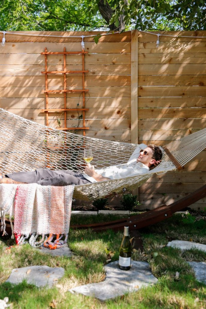 Man relaxing in a hammock next to a bottle of Chardonnay